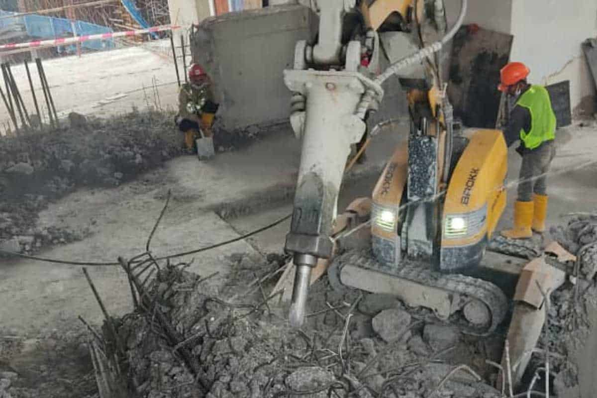 Demolition robot in action to remove tower crane foundation